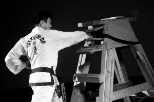 Photo of Tak smashing a plank of wood with his Taekwon-do skills