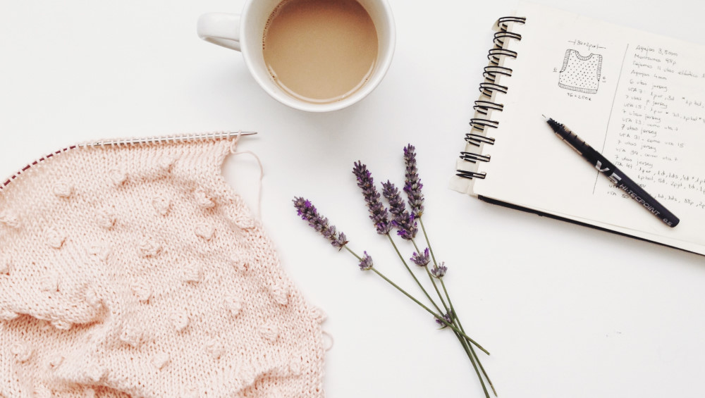 Photo of a knitted vest on a knitting needle, a sprig of lavender, a cup of tea, and a notebook with a knitting pattern written in it.