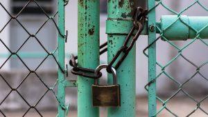 A padlock that locks a chain around a gate