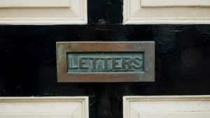 "A letter slot in a door that says ""Letters"""