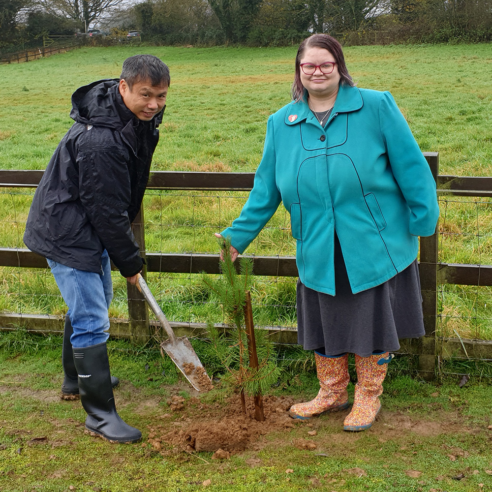 Tak and Kate in the rain planting a tree