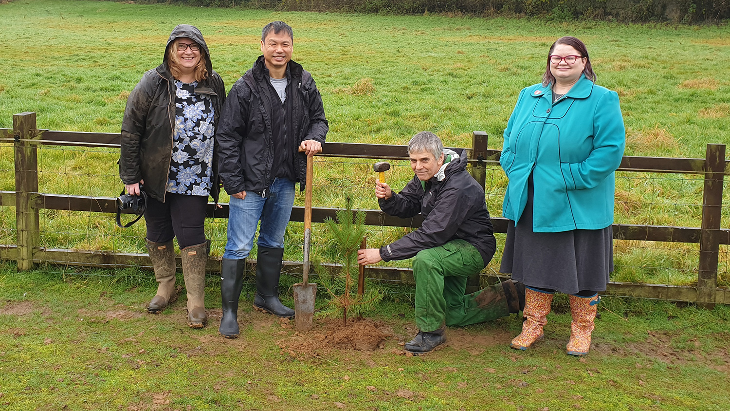 Liz, Tak, Hugh, and Kate stand next to a Scots pine tree being planted