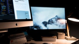 Photo of two monitors and a lamp in a darkened room.