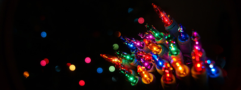 Multicoloured Christmas lights against a black background