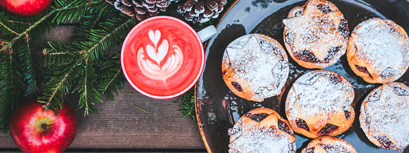 Mince pies and a hot beverage beside fir branches and apples