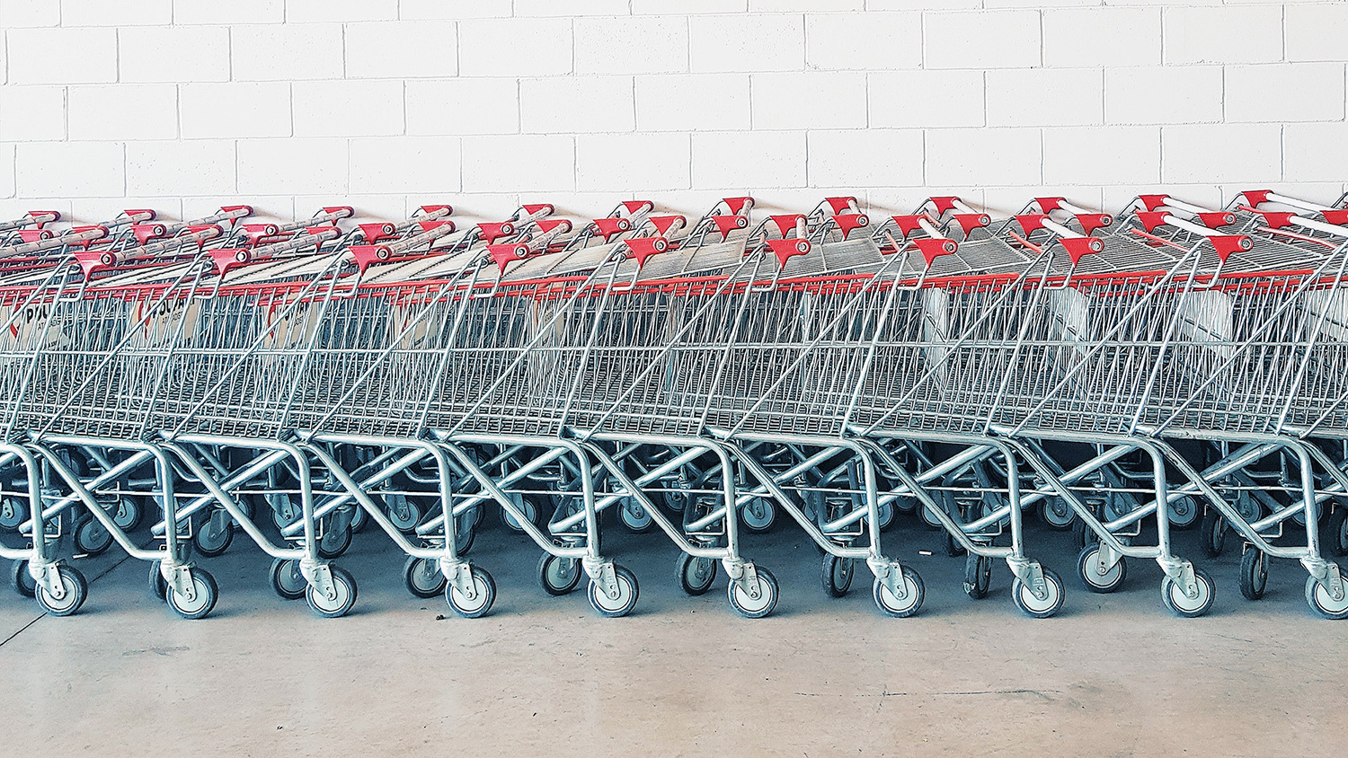 A row of shopping trolleys against a wall