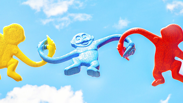 Three barrel of monkey toys against a blue sky background.