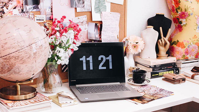 A home office desk with a laptop, a globe, a vase of flowers, books, dress mannequins, a coffee cup, and a wallet.