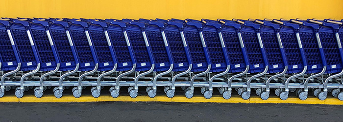 A row of blue shopping trolleys against a yellow wall.