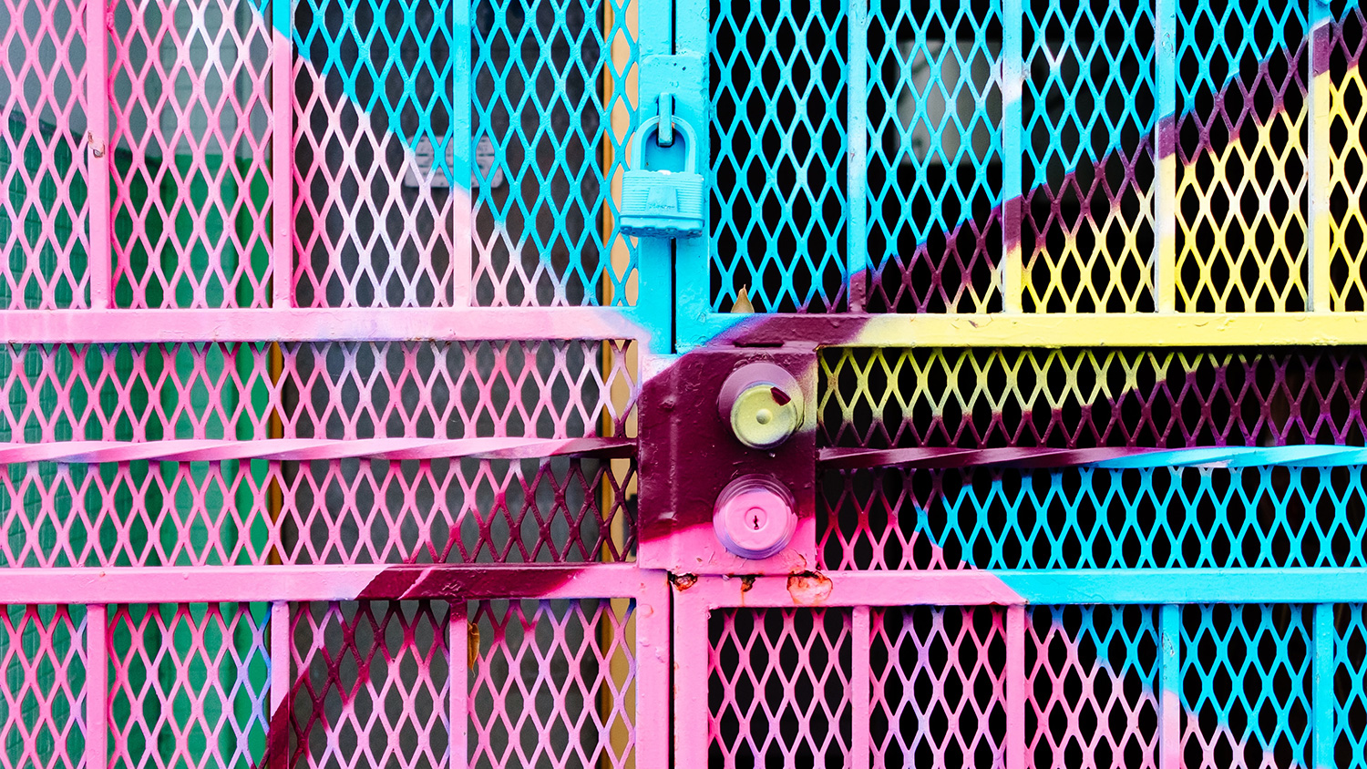 A brightly painted gate with a padlock and a door lock