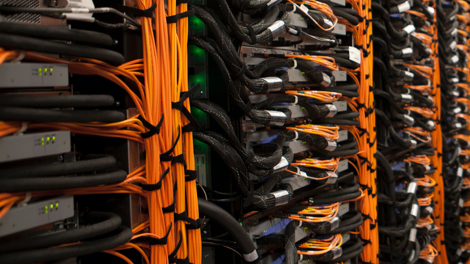 A row of servers cabled together with bright orange cables