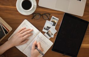 A person writes in a notebook on a desk strewn with photos, a notebook, a laptop, glasses, and a cup of coffee