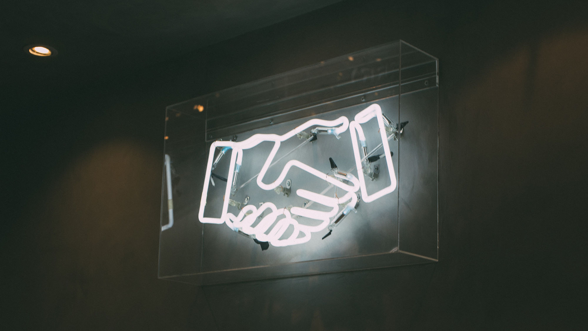 A neon sign of two hands shaking each other