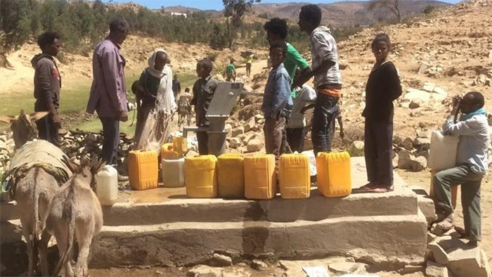 People waiting to use a water pump at a borehole well in Eritrea