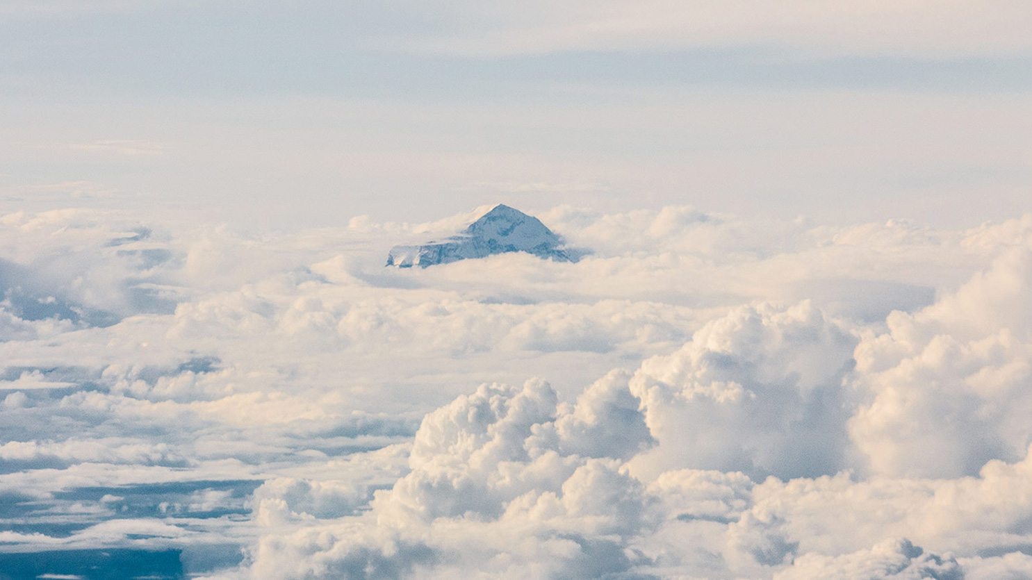 A mountain appearing out of white clouds
