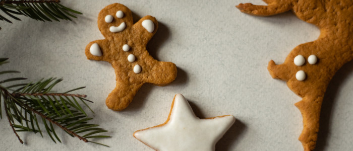 A gingerbread man and a gingerbread reindeer next to a frosted star cookie and some pine boughs