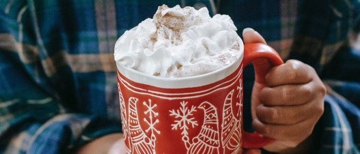 A child's hands holding a festive mug of hot cocoa covered in whipped cream