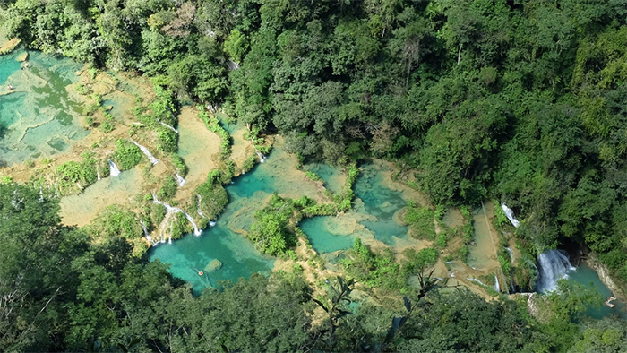 Sky view of a series of small pools and streams in a Mesoamerican jungle.