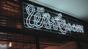 "A neon sign that says ""The Workroom"" above a door"