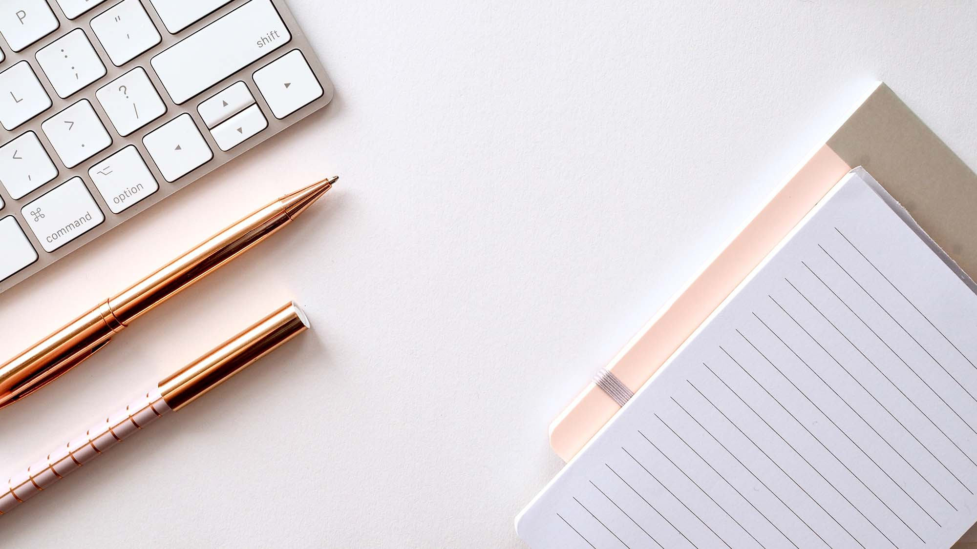 A keyboard, two rose gold pens, and a notepad on a desk