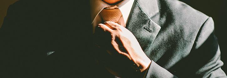 A man adjusting a tie.