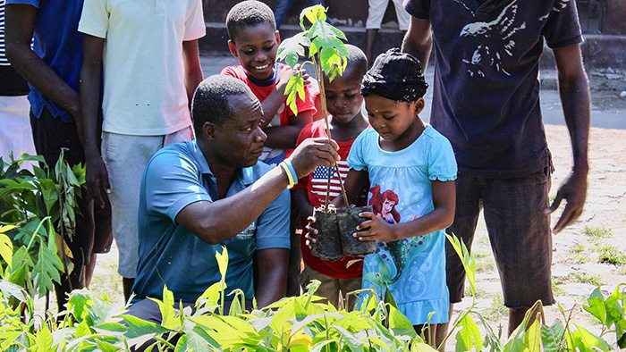 A man supports two saplings being held by a little girl as two boys look on.