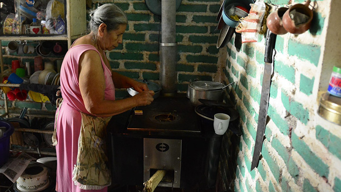 A woman stands in front of her new cook stove, preparing a meal.