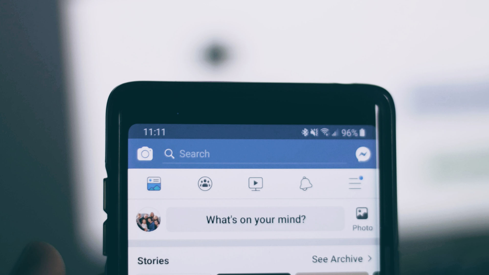 A phone is being held up with Facebook on the screen.