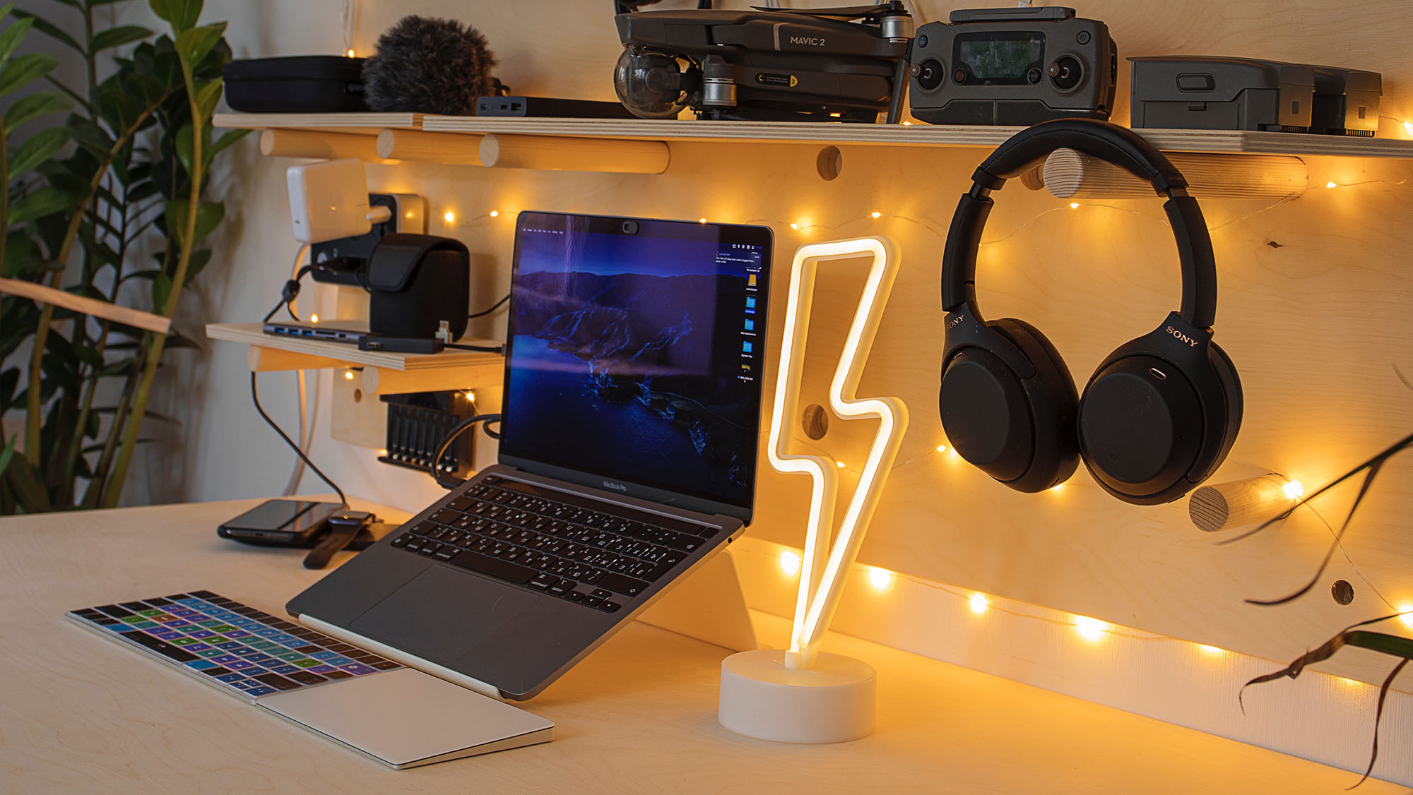 A desk with a lightning bolt lamp, headphones, and a laptop