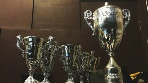 A row of trophies against a wood panel wall