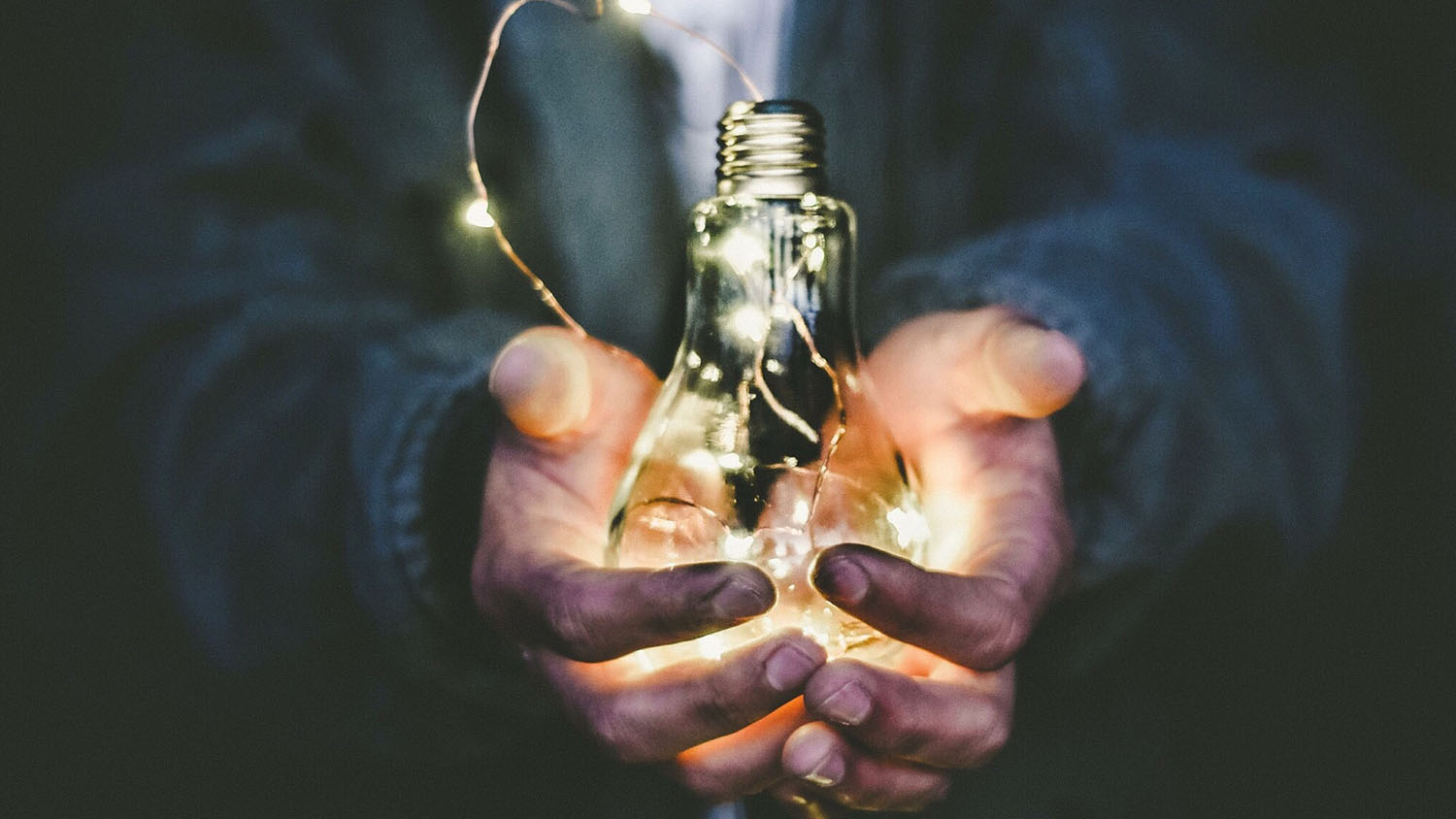 Two hands holding a light bulb lit by LEDs