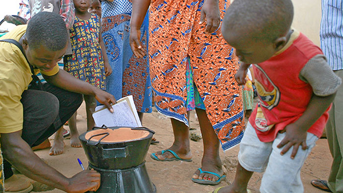 A small child watches someone show how to work one of the new Toyola cookstoves in a Ghanian village.